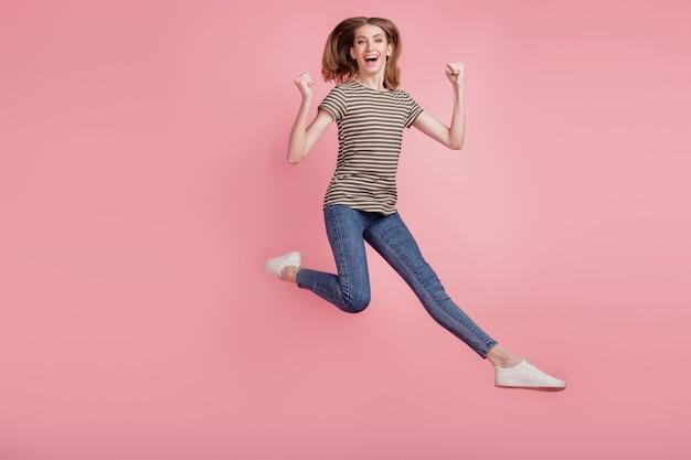 Full body portret van jonge vrouw gelukkig positieve glimlach verheugen overwinning vuisten handen springen geïsoleerd over roze kleur achtergrond