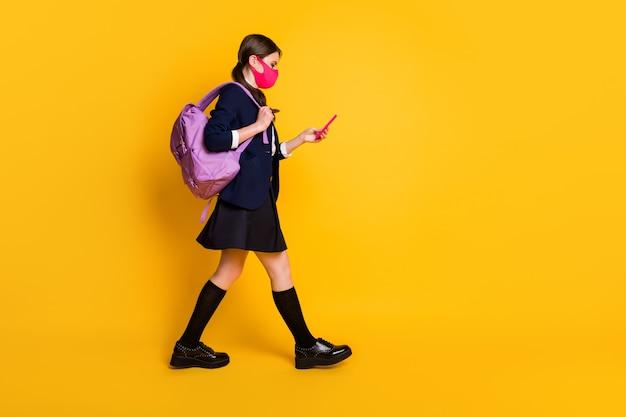 Full body profiel zijfoto middelbare school student meisje ga lopen gebruik smartphone