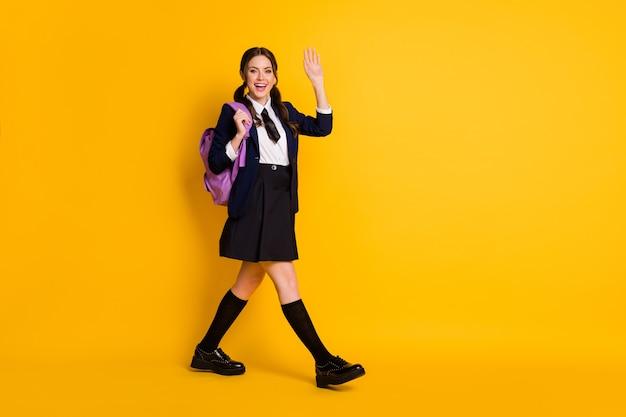 Full body profiel zijfoto van positieve middelbare school tiener go wave palm draagtas