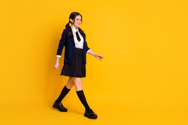 Full body profiel zijfoto van positieve universiteitsstudent go