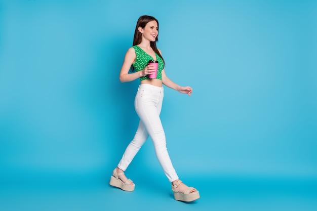 Full body profiel zijfoto van positieve vrolijke meid houd meeneem koffiekopje ga lopen copyspace draag tank-top sandalen geïsoleerd over blauwe kleur achtergrond