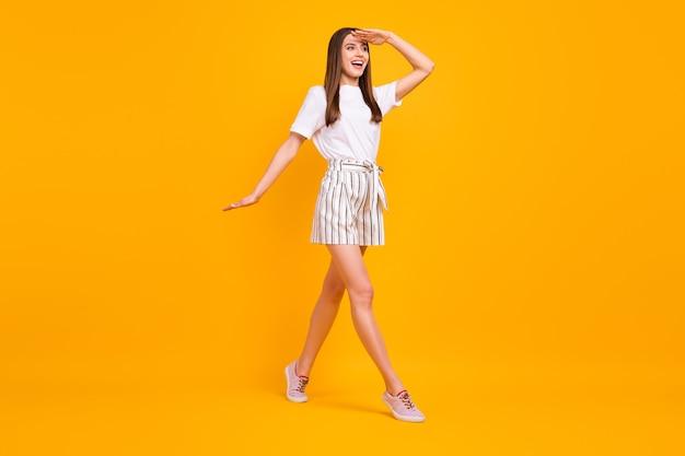 Full body profielfoto van aantrekkelijke grappige dame die door straat loopt genieten van zonnige dag kijken ver weg dragen casual wit t-shirt gestreepte korte broek schoenen geïsoleerd fel gele kleur muur
