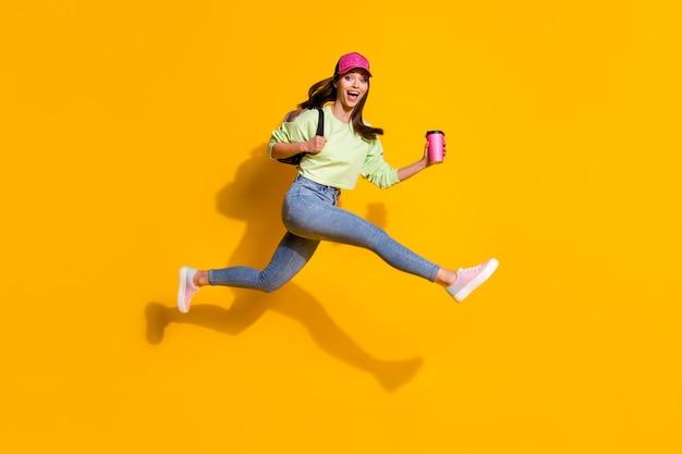 Full body profielfoto van energieke dame houdt rugzak afhaalkoffie sprong