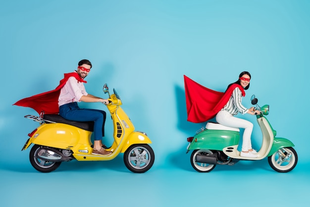 Full body profielfoto van gekke dame man rijden twee vintage bromfiets dragen rode cape masker haasten weg partij spelen superhelden rol jas vliegen lucht geïsoleerde blauwe kleur muur