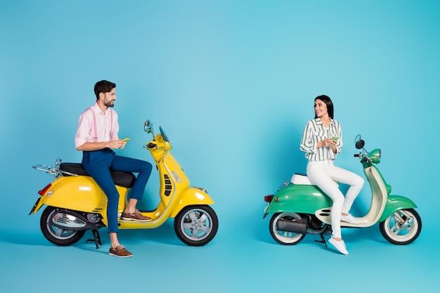 Full body profielfoto van grappige dame man twee mensen rijden twee vintage bromfiets samen browsen telefoon aanhankelijk gevoelens formalwear outfit geïsoleerde blauwe kleur muur