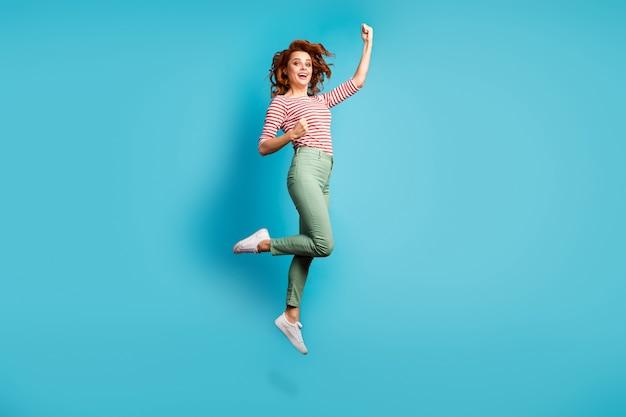 Full body profielfoto van grappige dame springen hoge vuisten winnen sportief kampioenschap vieren dragen casual rood wit overhemd groene broek schoenen geïsoleerde blauwe kleur