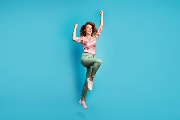 Full body profielfoto van grappige dame springen hoog verhogen vuisten winnen sportwedstrijd kampioenschap dragen casual rood wit shirt groene broek schoenen geïsoleerde blauwe kleur