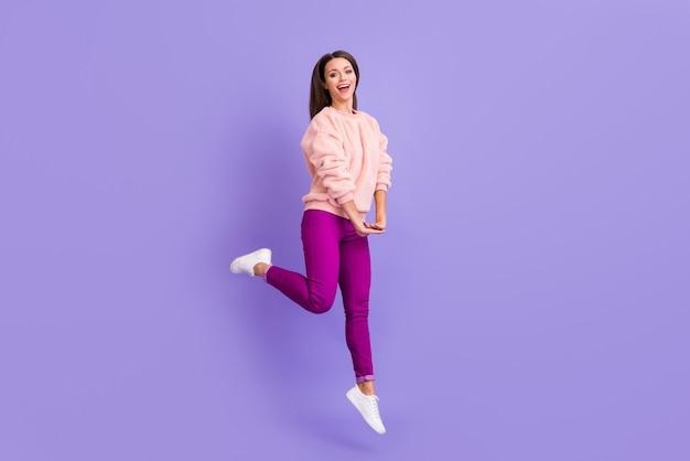Full body profielfoto van grappige extatische dame hoog springen verheugend