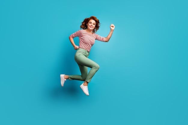 Full body profielfoto van mooie grappige dame sprong hoge snelheid haast laatste seizoen winkelen dragen casual rood wit overhemd groene broek schoeisel geïsoleerde blauwe kleur