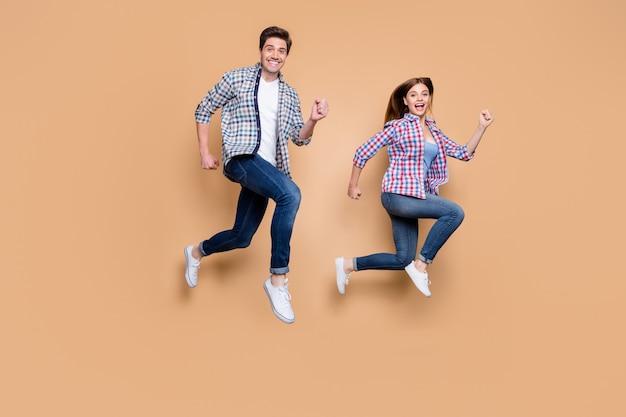 Full body profielfoto van twee mensen opgewonden dame man springen hoge haasten korting winkelen toeristen reizen dragen casual kleding geïsoleerde beige achtergrond