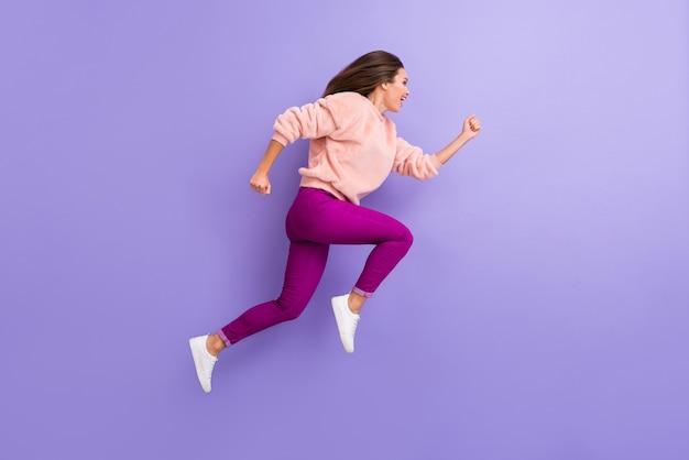 Full body profielfoto van vrolijke dame die hoogrennen race op paarse muur springt