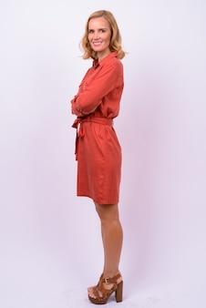 Full body shot profiel te bekijken van gelukkige blonde zakenvrouw camera kijken met gekruiste armen