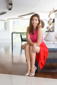 Full body shot van gelukkig mooie spaanse vrouw om thuis te zitten binnenshuis