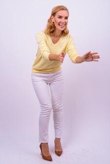 Full body shot van gelukkige mooie blonde zakenvrouw met opgeheven armen