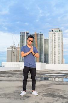 Full body shot van jonge knappe multi-etnische man met zonnebril tegen uitzicht over de stad