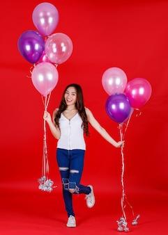 Full body shot van schattig en mooi aziatisch meisje dat kleurrijke luchtballonnen vasthoudt en speelt met een grappige en gelukkige glimlach op rode achtergrond, studiolichtopnamen. festival en vieren concept.