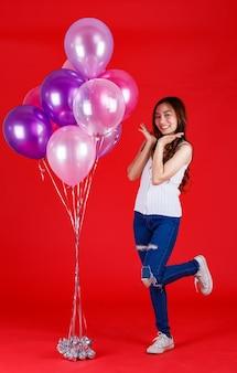 Full body shot van schattig en mooi aziatisch meisje dat staat en speelt met kleurrijke luchtballonnen met een grappige en gelukkige glimlach op rode achtergrond, studiolichtopnamen. festival en vieren concept.