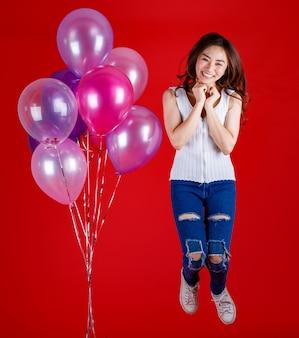 Full body shot van schattig en mooi aziatisch meisje springen en spelen met kleurrijke luchtballonnen met een grappige en gelukkige glimlach op rode achtergrond, studio licht schieten. festival en vieren concept.