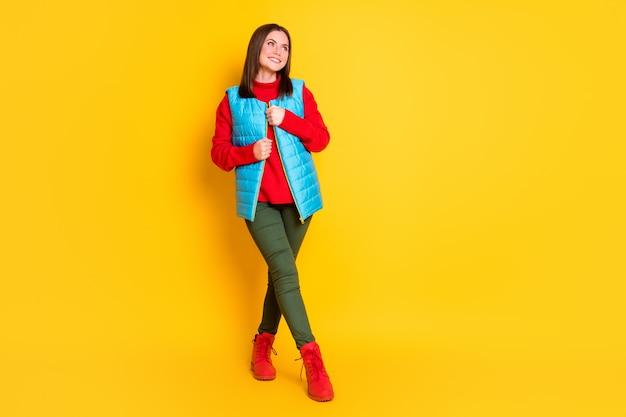 Full body size foto van schattige mooie jonge dame stralend glimlachen blik lege ruimte poseren horloge ster herfst dragen groene broek blauw vest rode trui laarzen geïsoleerd felgele kleur achtergrond