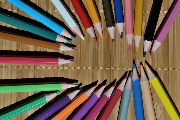 Full colour potloden in de vorm van een ellips op een houten ondergrond.
