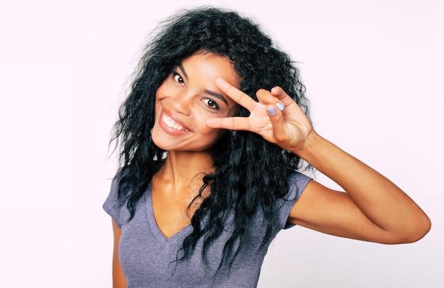 Full-face portret van dolblij afrikaanse etnische vrouw met amandelvormige donkere ogen en borstelig haar kijken naar de camera en tonen v-teken