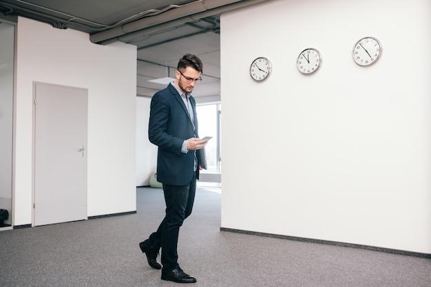 Full-lengh foto van aantrekkelijke man in glazen wandelen in kantoor. hij draagt een blauw shirt, een donker jasje, een spijkerbroek, zwarte schoenen en een baard. hij is aan het typen op de telefoon.