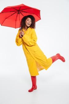 Full length beeld van vrolijke afrikaanse vrouw in regenjas