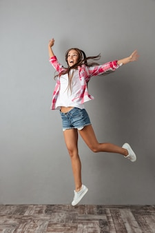 Full-length foto van mooie jonge vrouw in koptelefoon luisteren naar muziek en springen