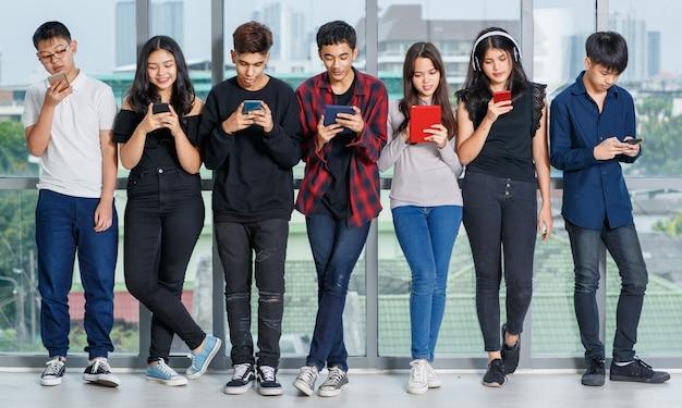 Full-length lichaamsportret van een groep van zeven jonge mannelijke en vrouwelijke tieners die staan en smartphones en tablet gebruiken zonder te praten. concept van technologie en telefoon verslaafd in adolescent