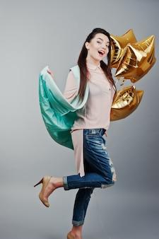 Full-length portret jonge brunette meisje draagt in roze blouse, turquoise jas, gescheurde spijkerbroek en crème schoenen met gouden ster ballonnen. mode studio-opname