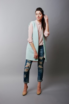 Full-length portret jonge brunette meisje draagt in roze blouse, turquoise jas, gescheurde spijkerbroek en crème schoenen