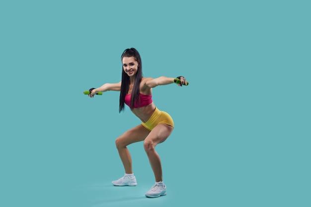 Full-length portret van een slanke vrouw fitnesstrainer die dumbbell squats uitoefent met uitgestrekte armen geïsoleerd op blauw oppervlak met kopie ruimte