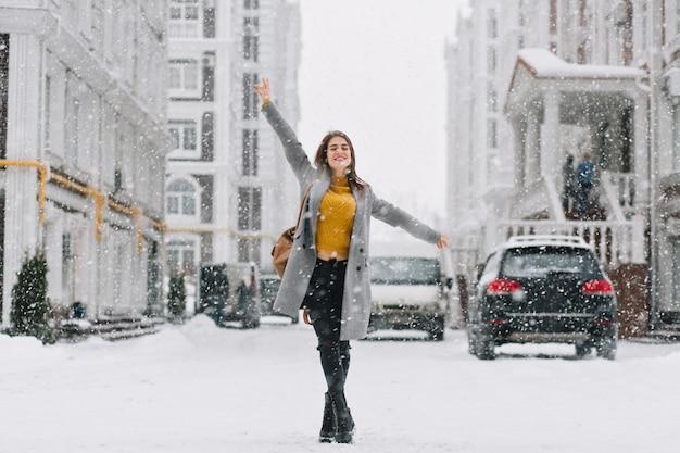 Full-length portret van geïnspireerd vrouwelijk model in stijlvolle jas poseren met plezier in winter stad. buitenfoto van blije blonde vrouw die van sneeuwval geniet tijdens wandeling door de stad.
