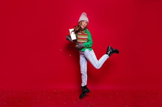 Full-length portret van gelukkige stijlvolle jonge dame gekleed groene trui, blauwe spijkerbroek, zwarte laarzen en grijze wintermuts springen met nieuwjaar presenteert op geïsoleerde rode achtergrond