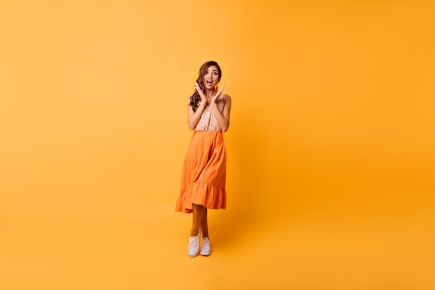 Full-length portret van geweldig meisje in heldere zomer outfit. blithesome brunette vrouw poseren op geel met verbaasde glimlach.