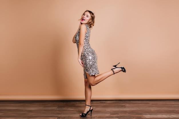 Full-length portret van gracieuze dame in trendy glanzende jurk met plezier in nieuwe schoenen met hoge hakken