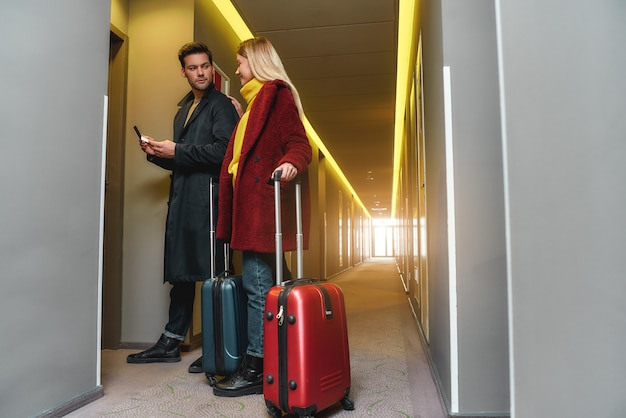 Full-length portret van jonge man en vrouw in vrijetijdskleding met koffers die hun kamer in een hotel binnenkomen. samen reizen concept. horizontaal schot. zijaanzicht
