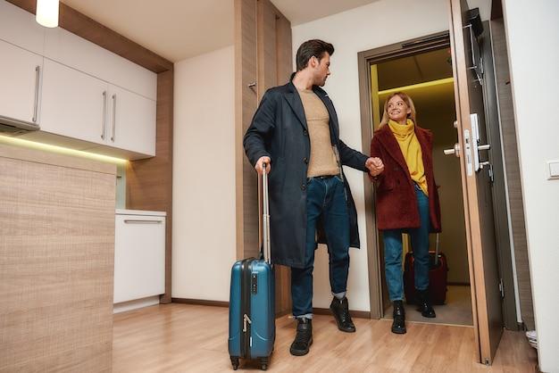 Full-length portret van jonge man en vrouw in vrijetijdskleding met koffers die hun kamer in een hotel binnenkomen. samen reizen concept. horizontaal schot