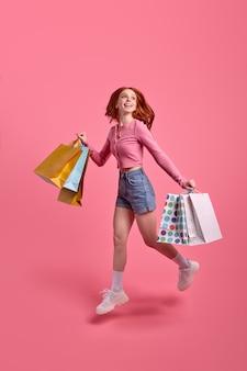 Full-length portret van schattige vrouw met pakketten hoog springen vieren weekend vakantie, kortingen in de winkel, zwarte vrijdag, casual roze shirt en denim shorts dragen, geïsoleerd op roze
