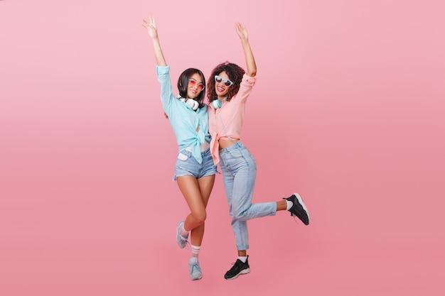 Full-length portret van slank afrikaans meisje in zwarte sneakers poseren op één been met europese brunette vriend. blanke jonge vrouw in blauw shirt grappig dansen met mulat dame.