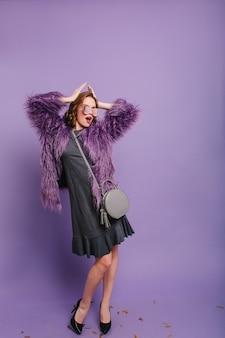 Full-length portret van slanke vrouw in casual grijze jurk en pluizig jasje poseren met handen omhoog