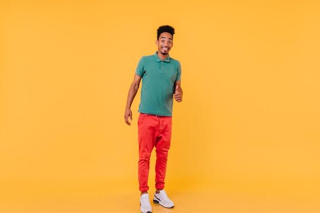 Full-length portret van stijlvolle afrikaanse man in witte sneakers. blij brunette man permanent in zelfverzekerde pose.