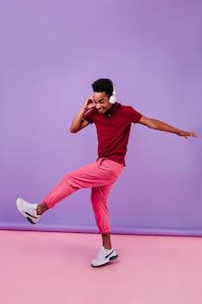 Full-length portret van stijlvolle geïnspireerde man dansen in koptelefoon. binnen schot van emotionele afrikaanse kerel die voor de gek houdt.