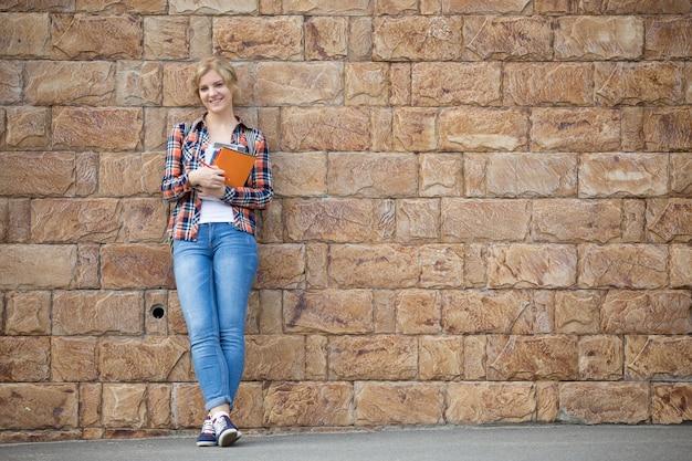 Full length portret van student meisje tegen de bakstenen muur met leerboeken
