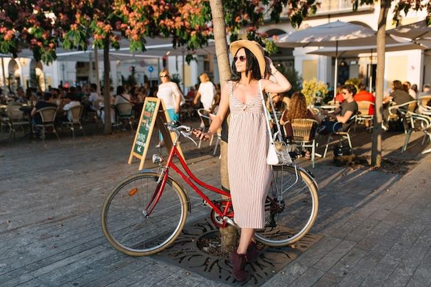 Full-length portret van trendy meisje in hoed en lange jurk staande op terras met fiets