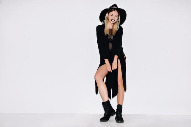Full-length portret van vrolijke stijlvolle moderne vrouw, gekleed in lange zwarte jaket en hoed, laarzen die zich over geïsoleerde muur bevinden