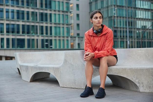Full-length shot van bedachtzame sportvrouw neemt pauze nadat buitensport denkt aan het bereiken van fitnessdoelen draagt windjack zwarte sneakers poses in het centrum van de stad