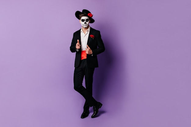 Full-length shot van charmante man met rode satijnen riem onder zwarte jas, poseren in halloween kostuum.