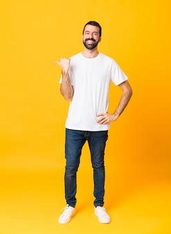 Full-length shot van de man met baard over geïsoleerde geel wijst naar de zijkant om een product te presenteren