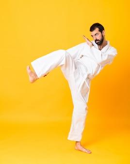 Full-length shot van mandoing karate over geel